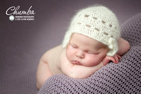 Close up newborn baby with chin on arms laying on a purple blanket with a white mohair crochet hat.